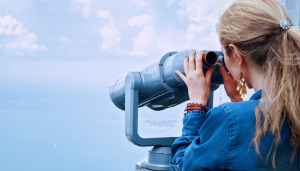 woman in blue denim jacket holding a gray steel tower viewer