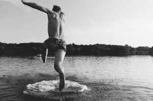 grayscale photography of man jumping on body of water
