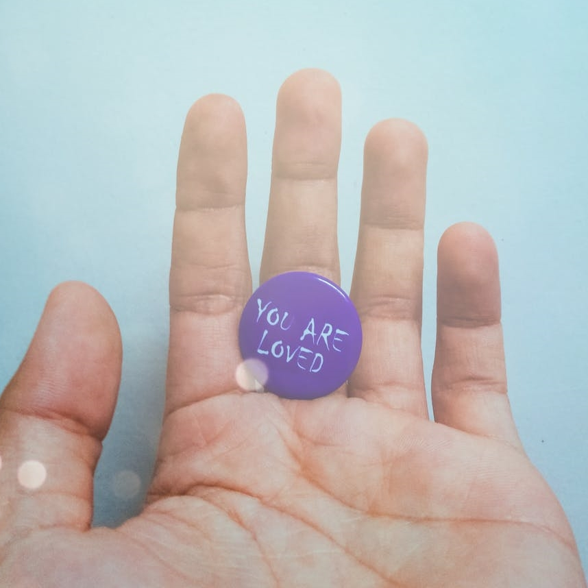 person holding purple badge you are loved text printed